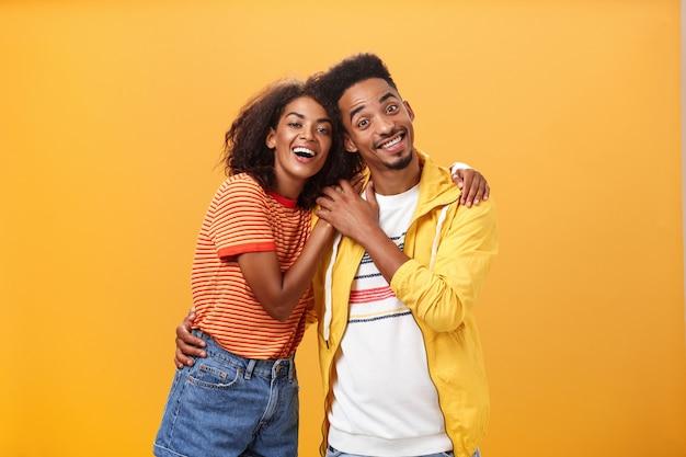 スタイリッシュで愛情のあるアフリカ系アメリカ人のカップルが広く抱き合って笑っています。