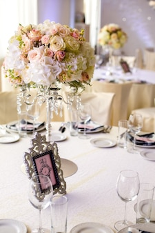 이벤트 손님을위한 세련되고 고급스러운 디자인의 식탁. 복숭아와 크림 장미, 크리스탈 샹들리에에 공 모양의 결혼식 구성의 흰색 수국