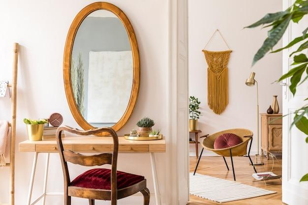 Стильный и минималистичный интерьер гостиной с дизайнерским золотым креслом, лампой, рамками для плакатов. туалетный столик с зеркалом, растениями, желтым макраме и аксессуарами в уютном домашнем декоре.