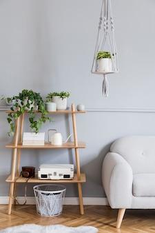 Стильный и минималистичный интерьер гостиной в стиле бохо с деревянной полкой, серым диваном, дизайнерскими и элегантными аксессуарами, вешалкой для кашпо ручной работы в стиле макраме. ботаника и домашний декор с множеством растений.