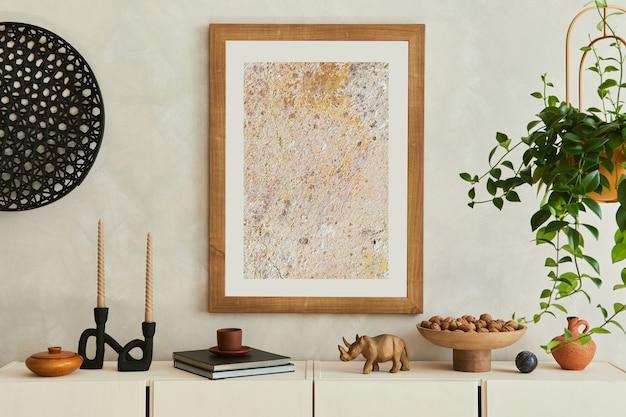 세련되고 현대적인 베이지색 거실 인테리어 구성은 모의 포스터 프레임, 베이지색 목재 사이드보드, 식물 및 보헤미안에서 영감을 받은 액세서리로 구성되어 있습니다. 주형.