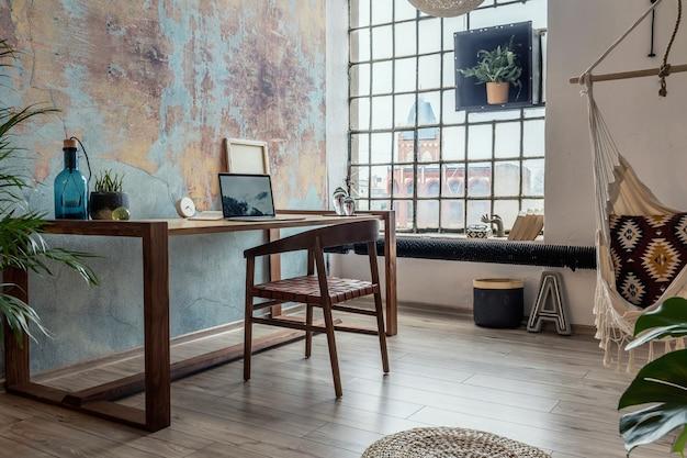 나무 테이블과 의자, 식물 및 액세서리가있는 창의적인 작업 공간 인테리어의 세련되고 현대적인 구성. 창의적인 벽과 쪽모이 세공 마룻 바닥을 갖춘 넓은 객실입니다.