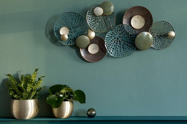 세련되고 현대적인 거실 구성. 선반이있는 녹색 벽 패널. 금 냄비, 장식 및 우아한 개인 액세서리의 아름다운 식물. 현대 가정 장식. 주형. 공간을 복사하십시오.
