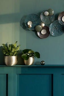세련되고 현대적인 거실 구성. 선반이 있는 녹색 벽 패널. 금 냄비, 장식 및 우아한 개인 액세서리의 아름다운 식물. 현대 가정 장식입니다. 주형. 공간을 복사합니다.