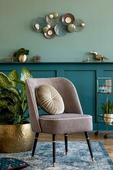 디자인 회색 안락 의자, 금색 주류 캐비닛, 큰 식물 및 우아한 개인 액세서리가 있는 세련되고 현대적인 거실 구성. 선반이 있는 회색 벽 패널. 현대 가정 장식입니다. 주형.