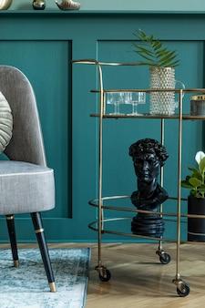 디자인 회색 안락의자, 금색 주류 캐비닛, 식물 및 우아한 개인 액세서리가 있는 세련되고 현대적인 거실 구성. 선반이 있는 회색 벽 패널. 현대 가정 장식입니다. 주형.