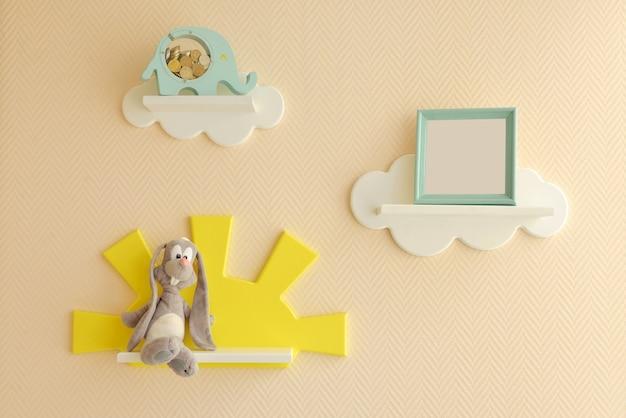 Стильный и современный дизайн интерьера. дом для детской комнаты. детские полочки в виде белых облаков на однотонной бежевой стене с фоторамкой и серым зайцем и копилкой.