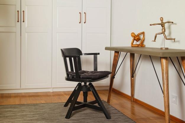 黒い椅子、デザイナーの白いワードローブ、テーブルを備えた、居心地の良いアパートの作業スペースのスタイリッシュでモダンなインテリア。室内装飾
