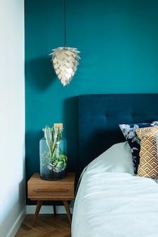 小さな木製のナイトテーブル、瓶の中の庭、白い寝具、色の枕と毛布を備えたスタイリッシュでモダンな日当たりの良いベッドルームのインテリア