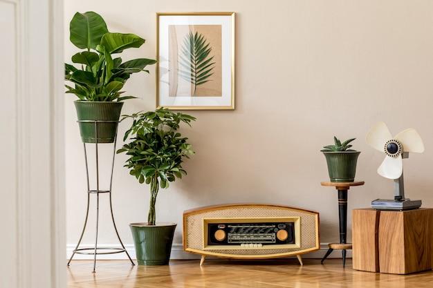 ゴールドのモックアップフレーム、ヴィンテージラジオ、ファン、エレガントなアクセサリー、植物の構成を備えた、スタイリッシュでレトロなインテリアの空間。居心地の良い家の装飾。ホームガーデン。リビングルームのベージュのコンセプト。テンプレート。