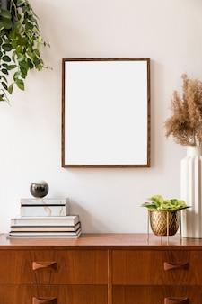 モックアップポスターフレーム、レトロなアクセサリー付きのヴィンテージ食器棚、花瓶のドライフラワー、植物を備えた家のインテリアのスタイリッシュでレトロな空間。ニュートラルな家の装飾。テンプレート。