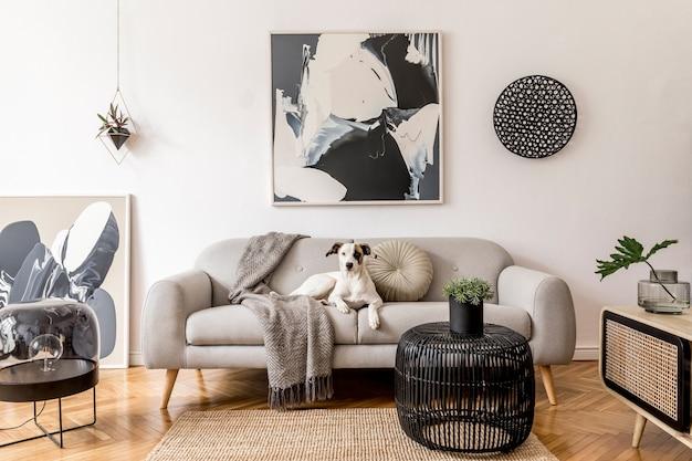 회색 소파, 디자인 나무 캐비닛, 블랙 테이블, 램프 및 벽에 추상 회화가있는 현대 아파트의 세련되고 스칸디나비아 거실 인테리어