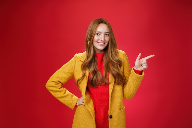 노란색 야외 코트에 주근깨가 있는 세련되고 자신감 있는 매력적인 빨간 머리 여성은 손가락 권총으로 오른쪽을 가리키고 빨간 벽 너머로 멋진 프로모션을 보여주면서 카메라처럼 즐겁게 웃고 있습니다.