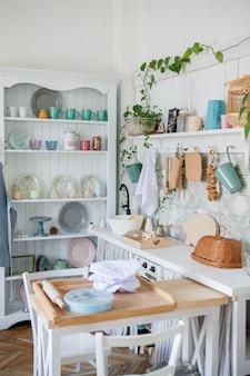 フォトスタジオで小さな木製のテーブルとキッチンスペースのスタイリッシュで日当たりの良いインテリア。キッチンアクセサリーを備えた北欧の部屋のインテリア。