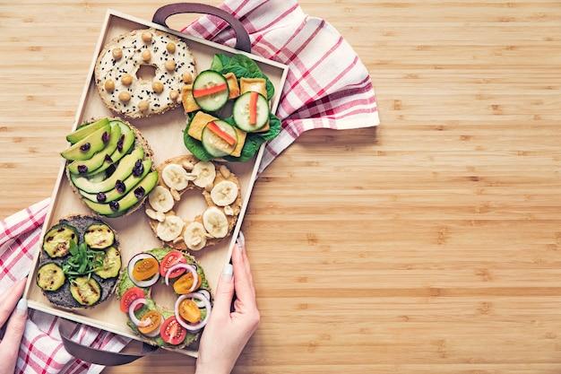 スタイリッシュでおいしいビーガン ベーグル サンドイッチ野菜ハーブ ペースト シード フムスと木製のテーブルの上にレタスの塩焼き 新鮮でヘルシーな朝食 コピー スペース トップ ビュー