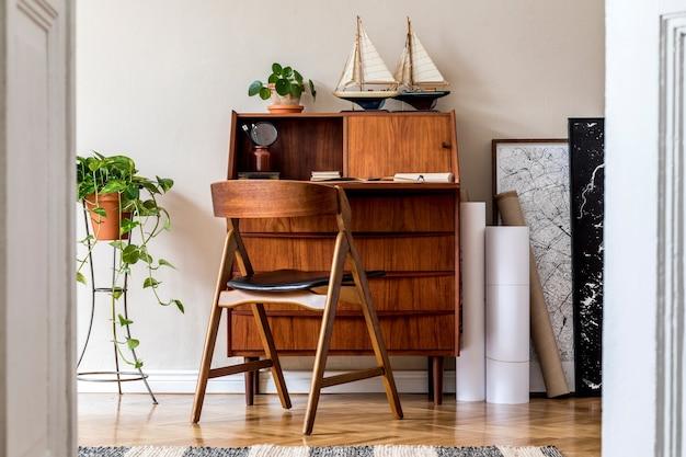 Стильный и винтажный дизайн интерьера гостиной с деревянным ретро комодом, растениями, кораблями, картой и элегантными личными аксессуарами. Premium Фотографии