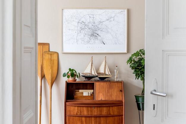 木製のレトロな便器、植物、船、櫂、地図、エレガントなパーソナルアクセサリーを備えたリビングルームのスタイリッシュでヴィンテージなインテリアデザイン。壁にポスターフレームをモックアップします。テンプレート。室内装飾。