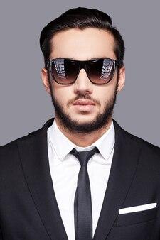 スタイリッシュで若い。灰色の背景に立っている間カメラを見ているサングラスと正装でハンサムな若い男の肖像画