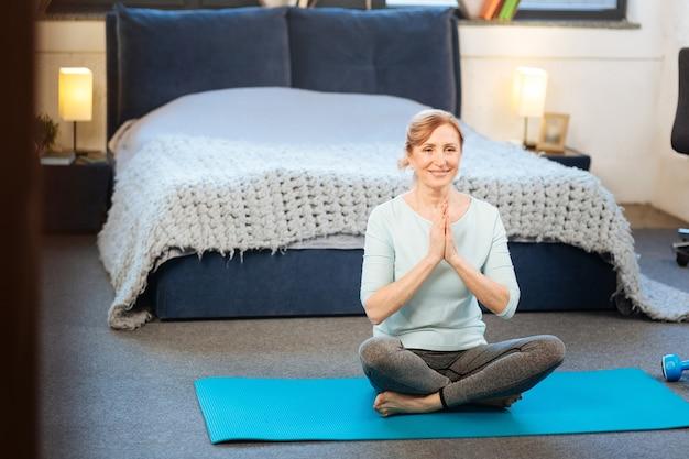 スタイリッシュなアパート。彼女の寝室の床でヨガをしている柔らかい笑顔でポジティブな平和な大人の女性