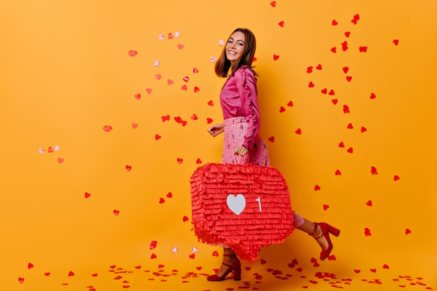 Стильная привлекательная девушка позирует с вдохновенной улыбкой. веселая блогерша в розовой блузке смеется под конфетти.