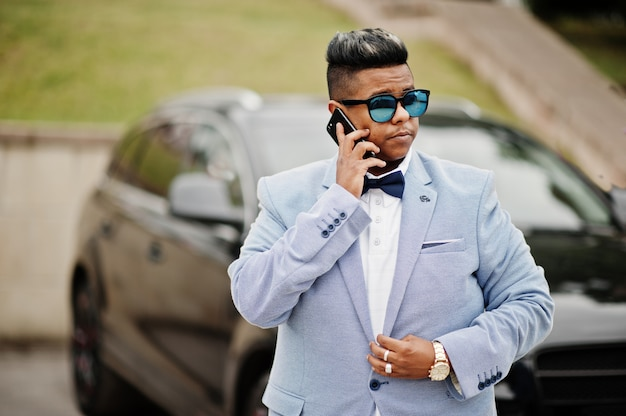 Stylish arabian man in jacket, bow tie and sunglasses against black suv car. arab rich speaking on mobile phone.