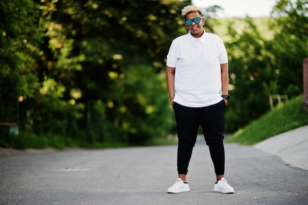 Stylish arabian muslim boy with originally hair and sunglasses posed on streets.