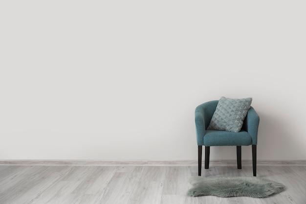 Стильное кресло с подушкой у светлой стены в комнате