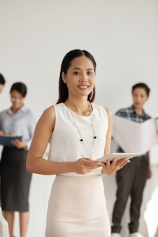 Стильная азиатская коммерсантка представляя с таблеткой, и коллеги стоя позади