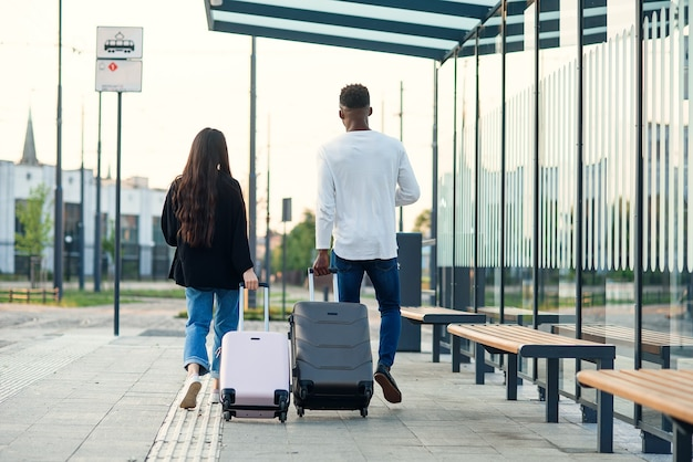 スタイリッシュなアジアの女の子と黒人の男が、チケット付きのパスポートを持ってバス停を歩いている車輪にスーツケースを持っています。