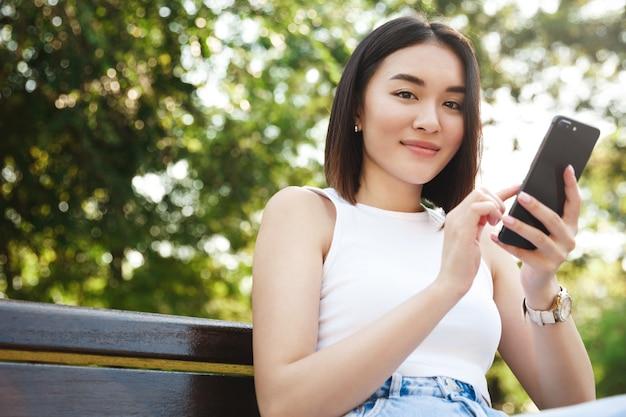 公園に座ってスマートフォンを使用して、カメラに微笑んでスタイリッシュなアジアの女の子