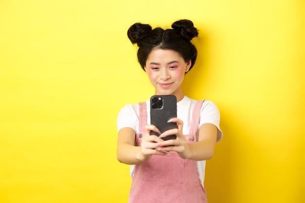 세련 된 아시아 여자 스마트 폰 사진을 찍고, 핸드폰으로 비디오를 만들고 웃 고, 노란색에 서.