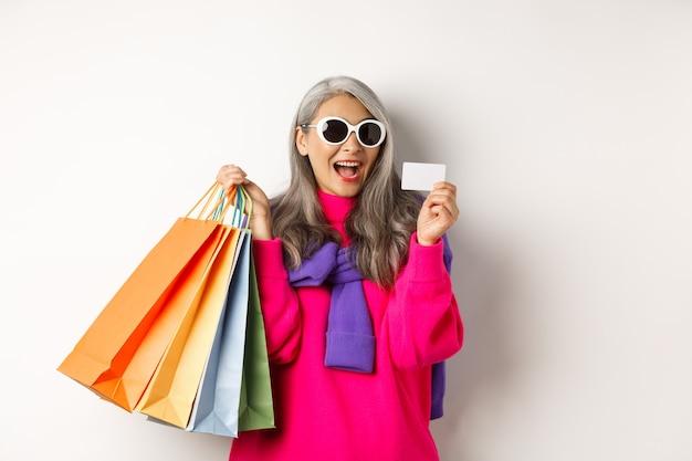 Elegante nonna asiatica in occhiali da sole che va a fare shopping durante i saldi delle vacanze, con in mano sacchetti di carta e carta di credito in plastica, in piedi su sfondo bianco.