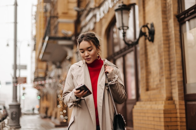Stylish asian lady in beige coat, red top and cross-body bag walks around city, holding smartphone.