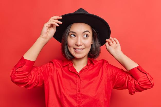 アウトドアウォーク用の黒い帽子と赤いシャツのドレスを着たスタイリッシュなアジアの女性は、明るいスタジオでの将来のポーズについて下唇が何かを噛むことを想像しています