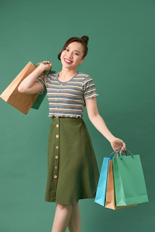 Stylish asian woman smiling and holding shopping bags