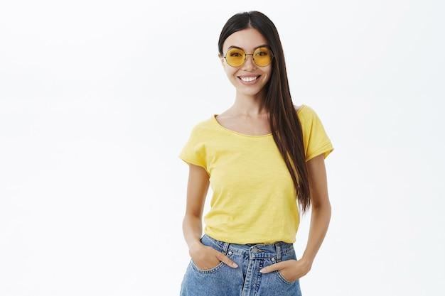 Elegante fashion blogger femminile dall'aspetto assertivo e fiducioso in occhiali da sole gialli alla moda che tengono le mani in tasca