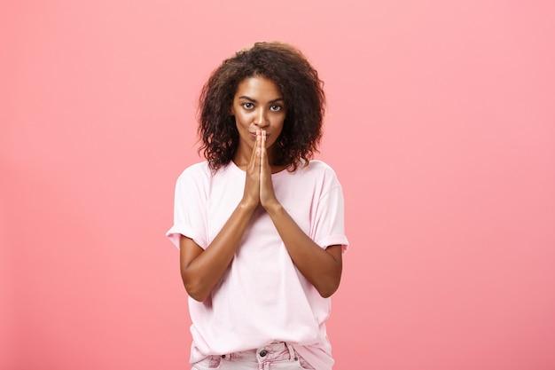 面白い表情で手をつないで巻き毛の髪型を持つスタイリッシュな魅力的なアフリカ系アメリカ人の女性。