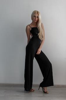 검은 세련된 세련된 정장과 신발에 긴 금발 머리를 가진 세련된 매력적이고 섹시한 여자가 흰색 방에 서 있습니다.