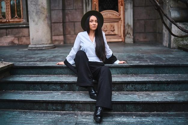 Стильная привлекательная элегантная женщина, сидящая на лестнице старого старинного здания