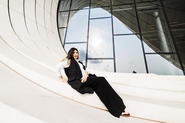 바쿠 시의 특이한 건물을 배경으로 포즈를 취한 검은 양복을 입은 세련된 매력적인 소녀