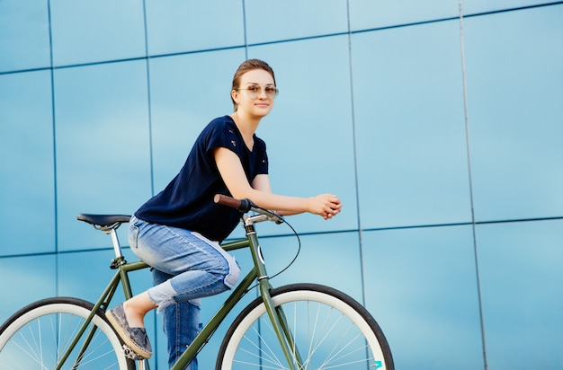 Stylish attractive girl in sunglasses on a bicycle. dressed in fashionable jeans and t-shirt. outdoors.