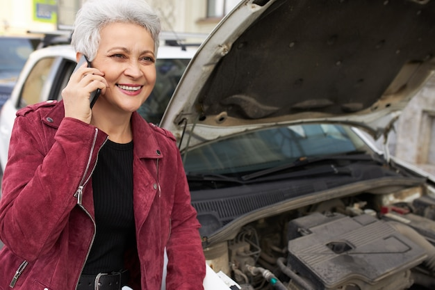 Driver femminile maturo dai capelli grigi attraente alla moda in piedi vicino alla sua automobile bianca rotta con il cofano aperto e parlando al telefono