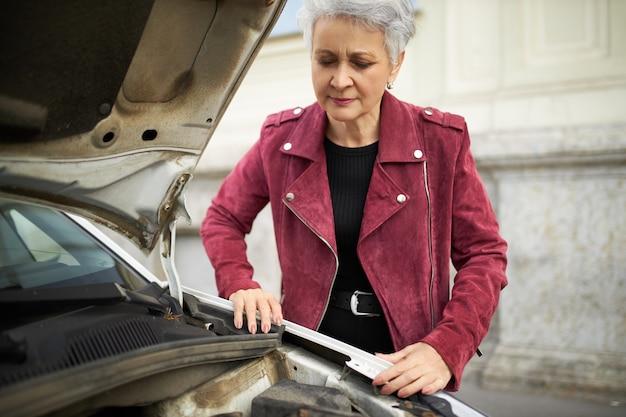 오픈 후드와 함께 그녀의 깨진 흰색 차 근처에 서 세련된 매력적인 회색 머리 성숙한 여성 드라이버