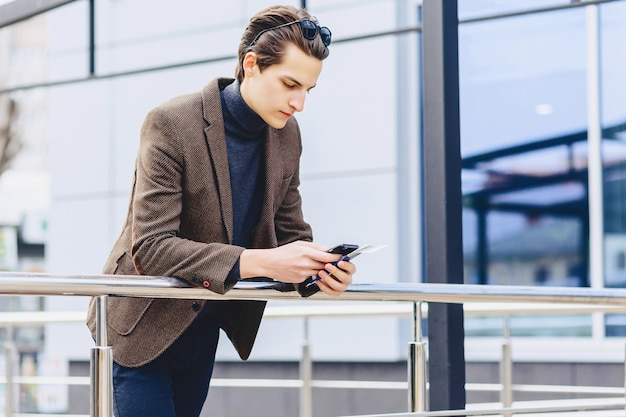 Stylish attractive guy in jacket with phone passport and tickets