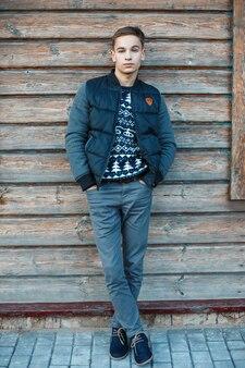 겨울 부츠에 세련된 청바지에 파란색 니트 스웨터에 트렌디 한 재킷이 달린 세련된 헤어 스타일로 세련된 매력적인 남자가 야외 나무 빈티지 벽 근처에 서 있습니다. 좋은 녀석.