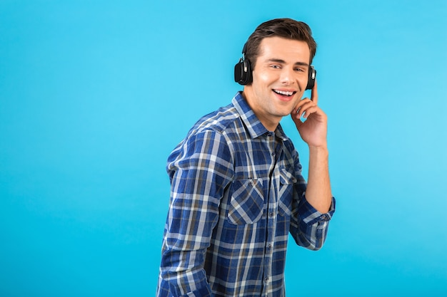 Stylish attractive handsome young man listening to music on wireless headphones