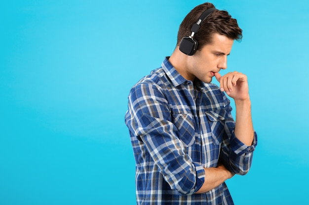 Стильный привлекательный красивый молодой человек слушает музыку в беспроводных наушниках