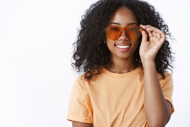 Elegante attraente moderno urbano trendy ragazza dalla carnagione scura che indossa occhiali da sole cool sorridente felice pronto a prendere il sole vicino alla piscina fantastico clima soleggiato che esprime felicità gioia delizia
