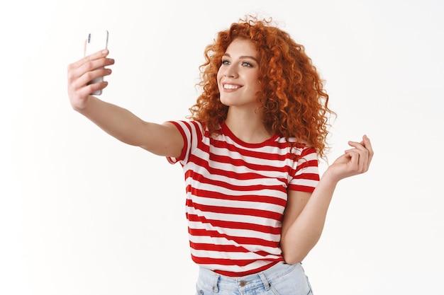 세련되고 매력적인 빨간 머리 곱슬머리 소녀 유행하는 파업 포즈는 셀카를 찍는 스마트폰을 들고 소셜 미디어 추종자들을 보여주는 새로운 여름 옷이 활짝 웃고 있는 흰 벽을 보여줍니다.