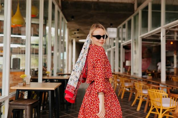Elegante donna attraente che cammina in abito rosso estivo con accessori in testa nella caffetteria estiva